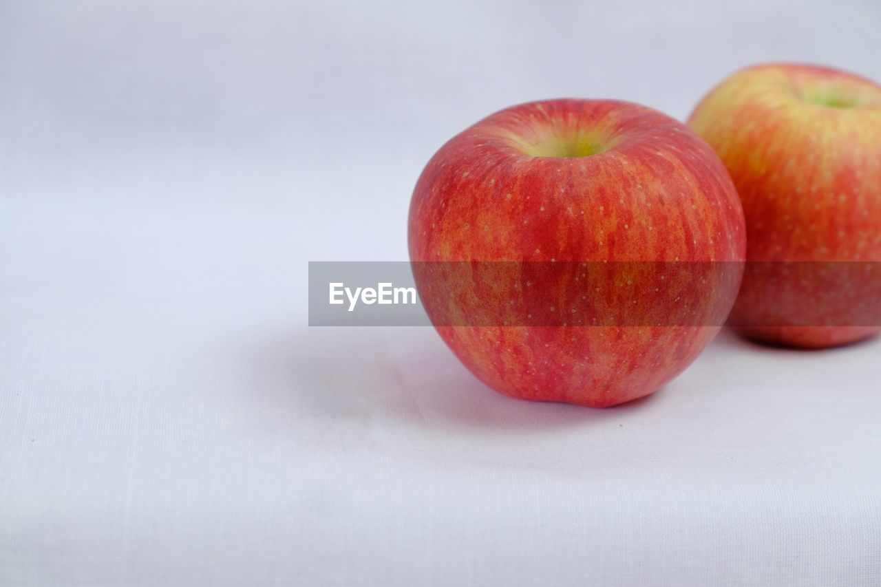 healthy eating, fruit, food and drink, food, wellbeing, freshness, still life, red, close-up, no people, apple - fruit, indoors, studio shot, table, single object, copy space, white background, selective focus, focus on foreground, two objects