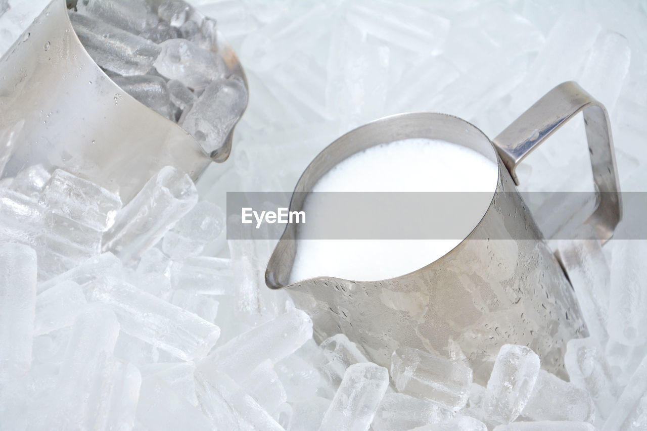 High angle view of milk in jug amidst ice cubes