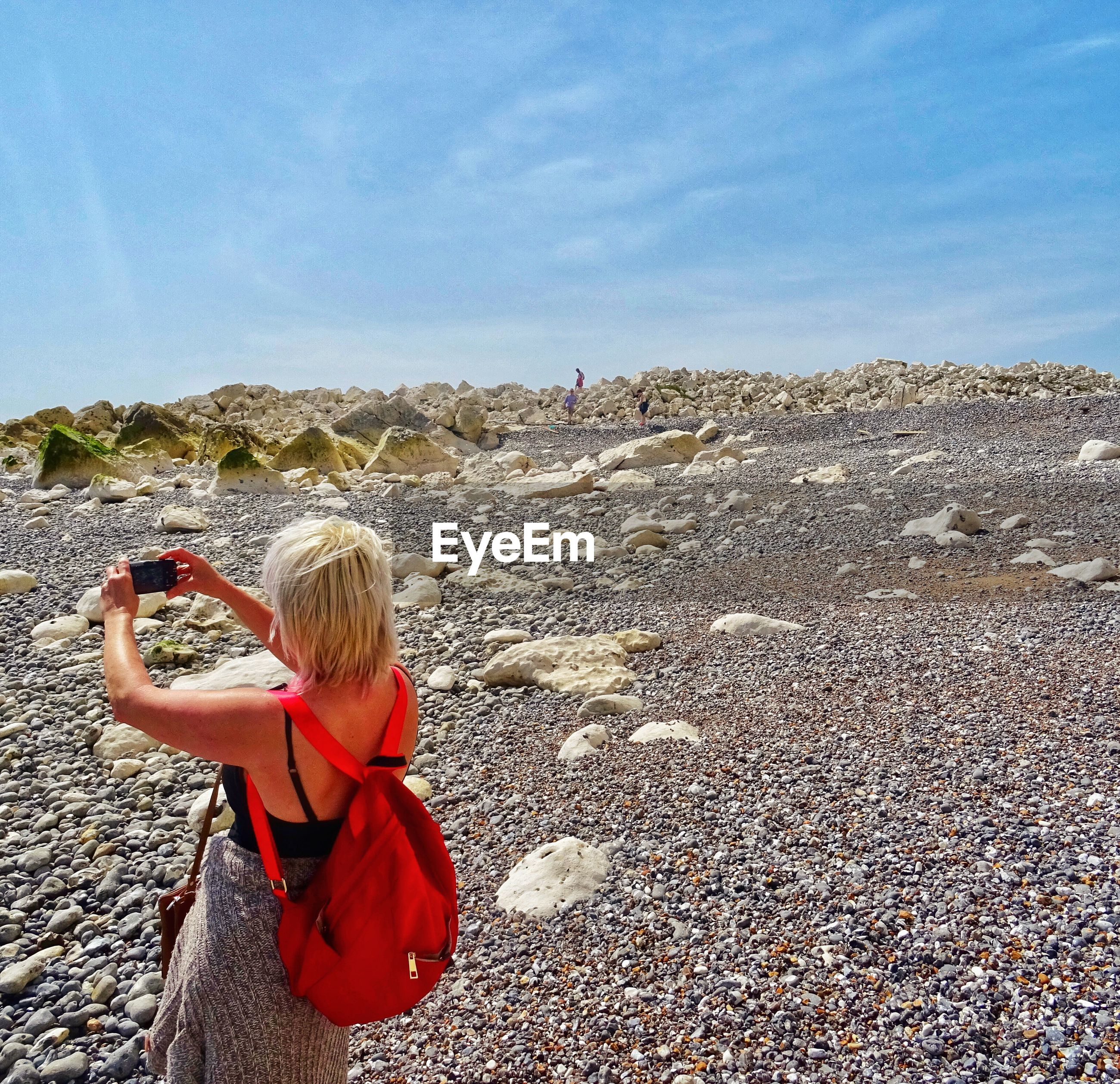 Woman photographing through mobile phone while standing on landscape