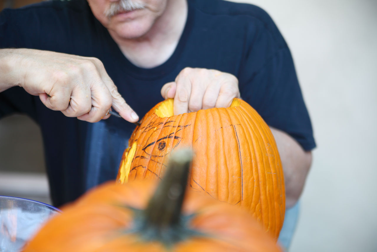 View Of Old Man Carving A Pumpkin For Halloween