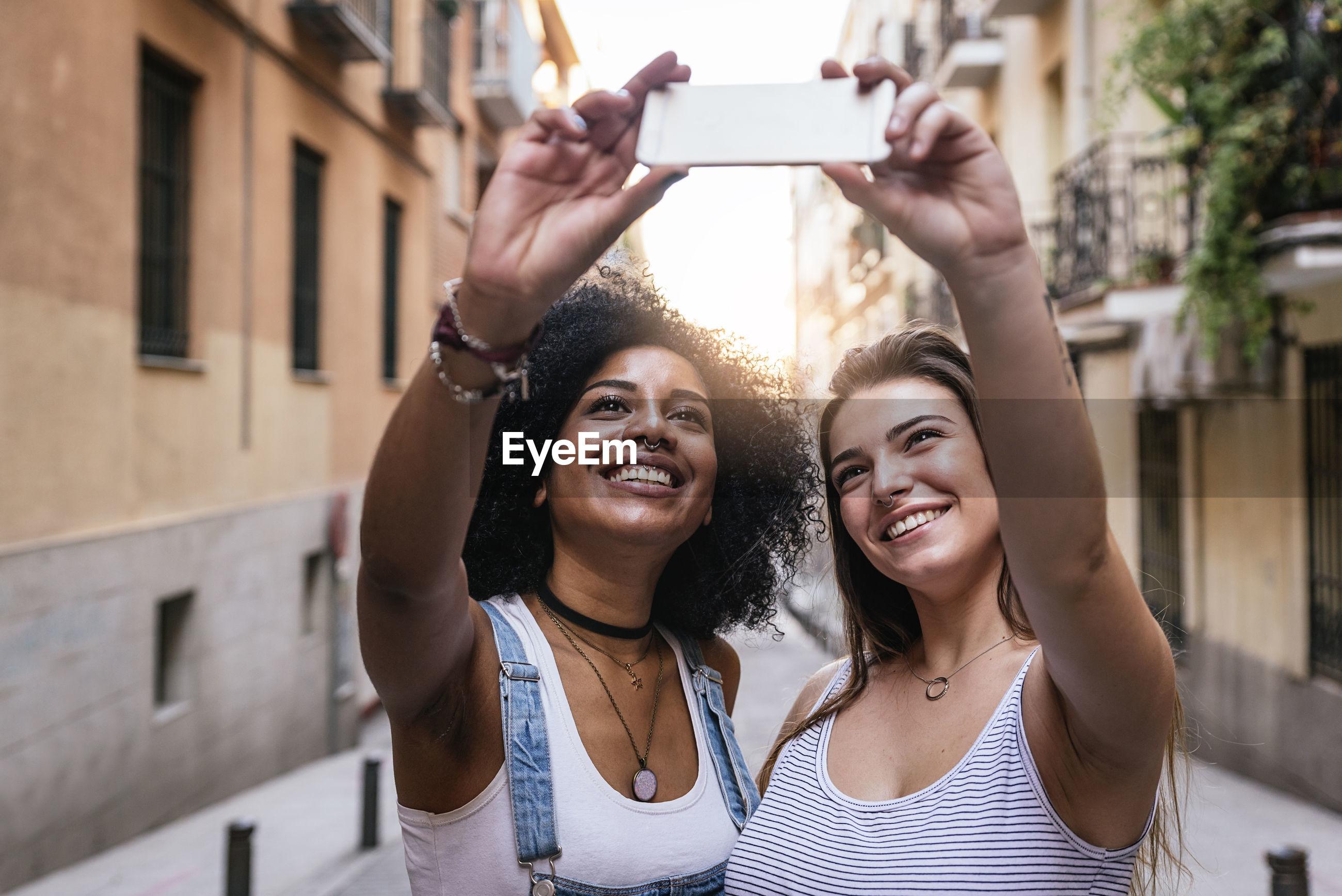 Smiling friends talking selfie in city