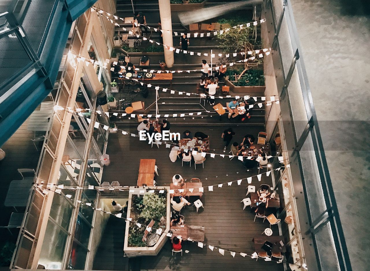 high angle view, group of people, crowd, large group of people, real people, transportation, architecture, indoors, men, city, escalator, shopping mall, built structure, staircase, women, lifestyles, modern, mode of transportation