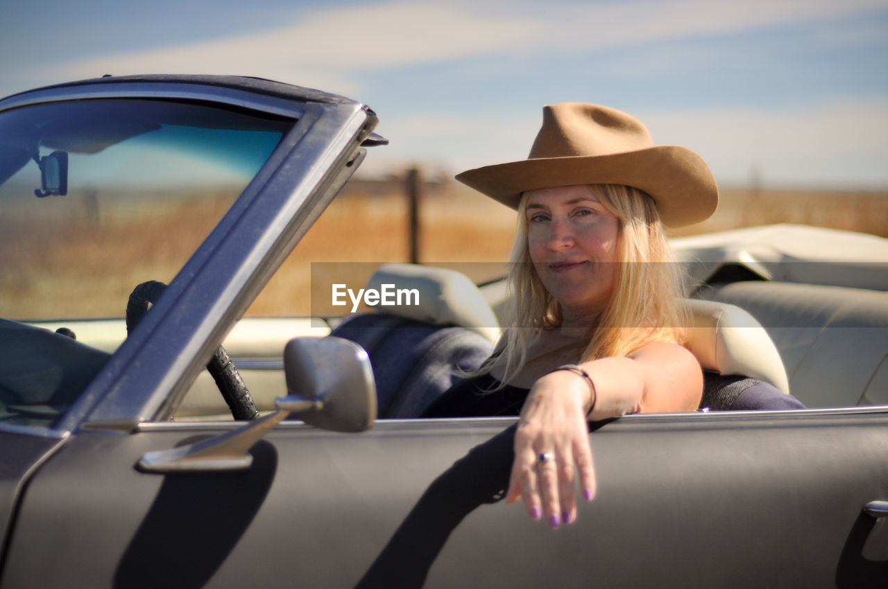 car, mode of transportation, motor vehicle, transportation, land vehicle, portrait, lifestyles, smiling, leisure activity, real people, women, hat, travel, young adult, one person, adult, convertible, day, sitting, hair, beautiful woman, cowboy hat, hairstyle