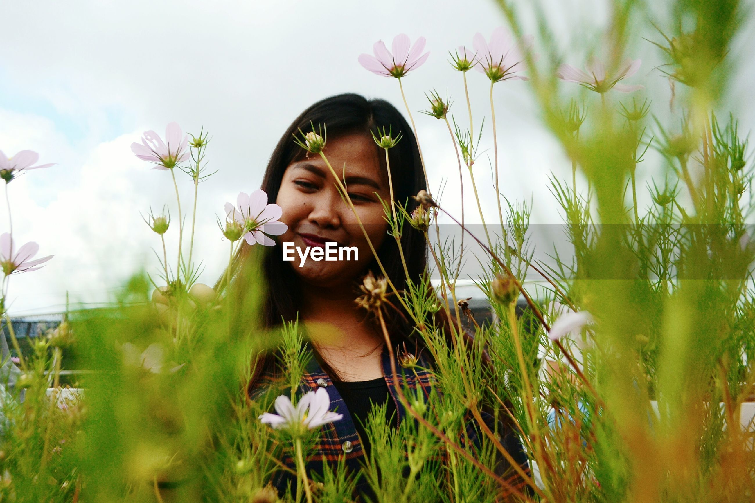PORTRAIT OF BEAUTIFUL YOUNG WOMAN ON FIELD BY FLOWERING PLANTS