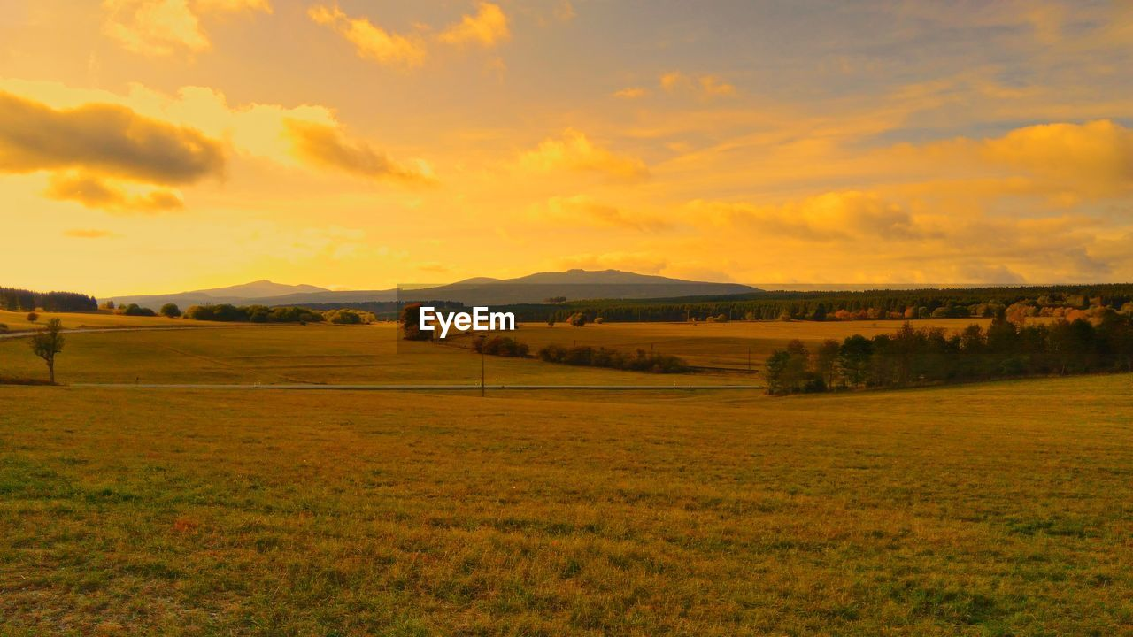 sky, environment, beauty in nature, landscape, scenics - nature, land, tranquil scene, cloud - sky, field, tranquility, plant, sunset, nature, grass, non-urban scene, no people, idyllic, orange color, mountain, outdoors