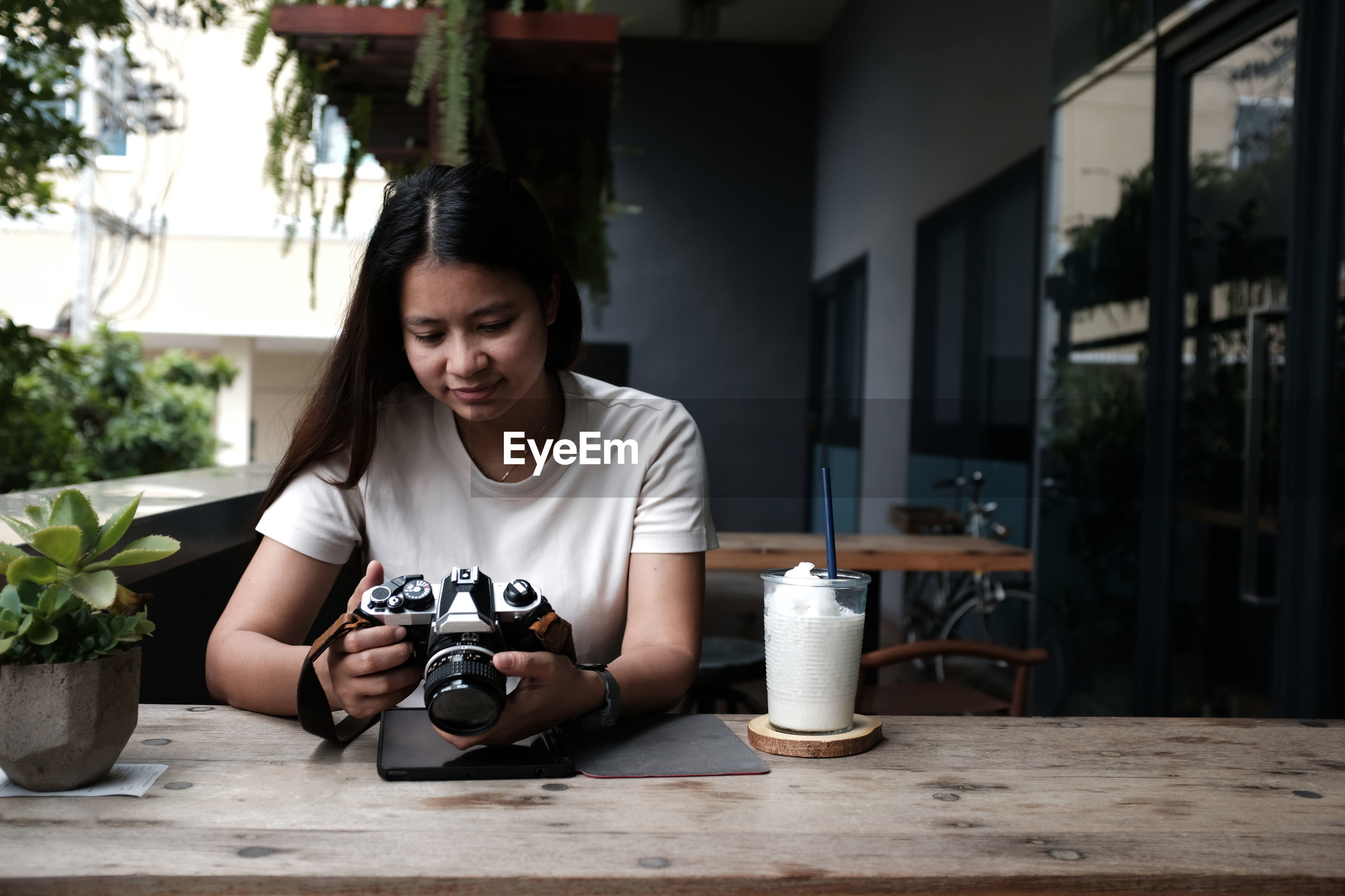 A beautiful asian woman is holding a camera. and sitting in a coffee shop