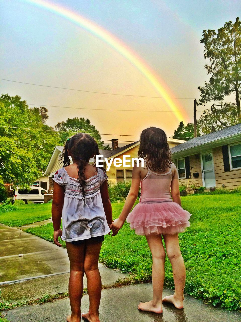 rainbow, real people, full length, building exterior, rear view, built structure, house, leisure activity, two people, tree, casual clothing, standing, girls, togetherness, outdoors, day, bonding, architecture, childhood, happiness, grass, sky, bubble wand