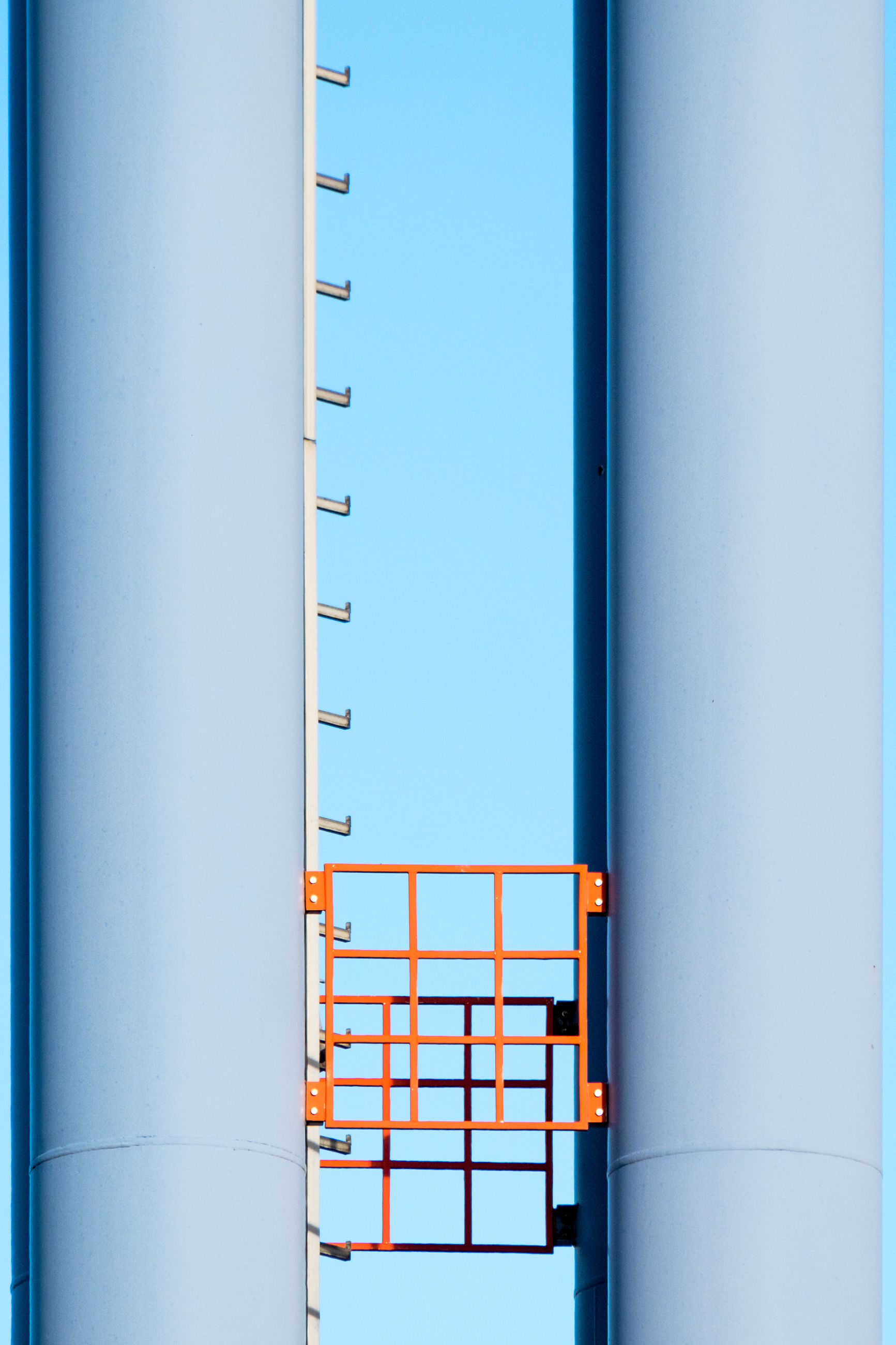 Low angle view of silos against blue sky