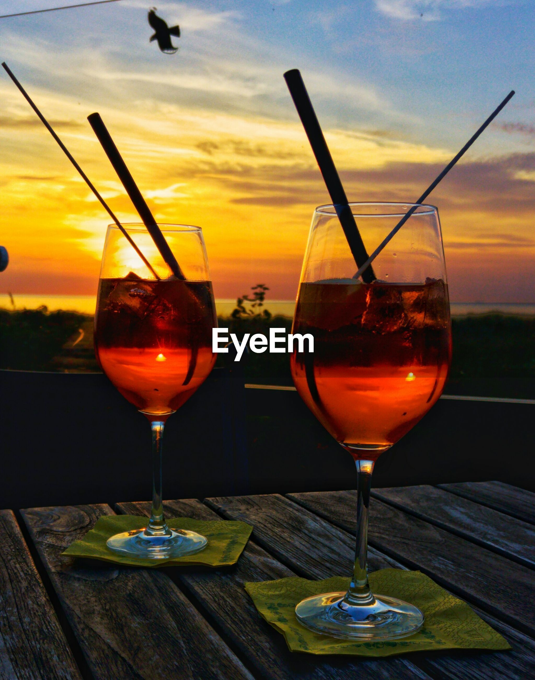 Wine glasses on table against sky during sunset