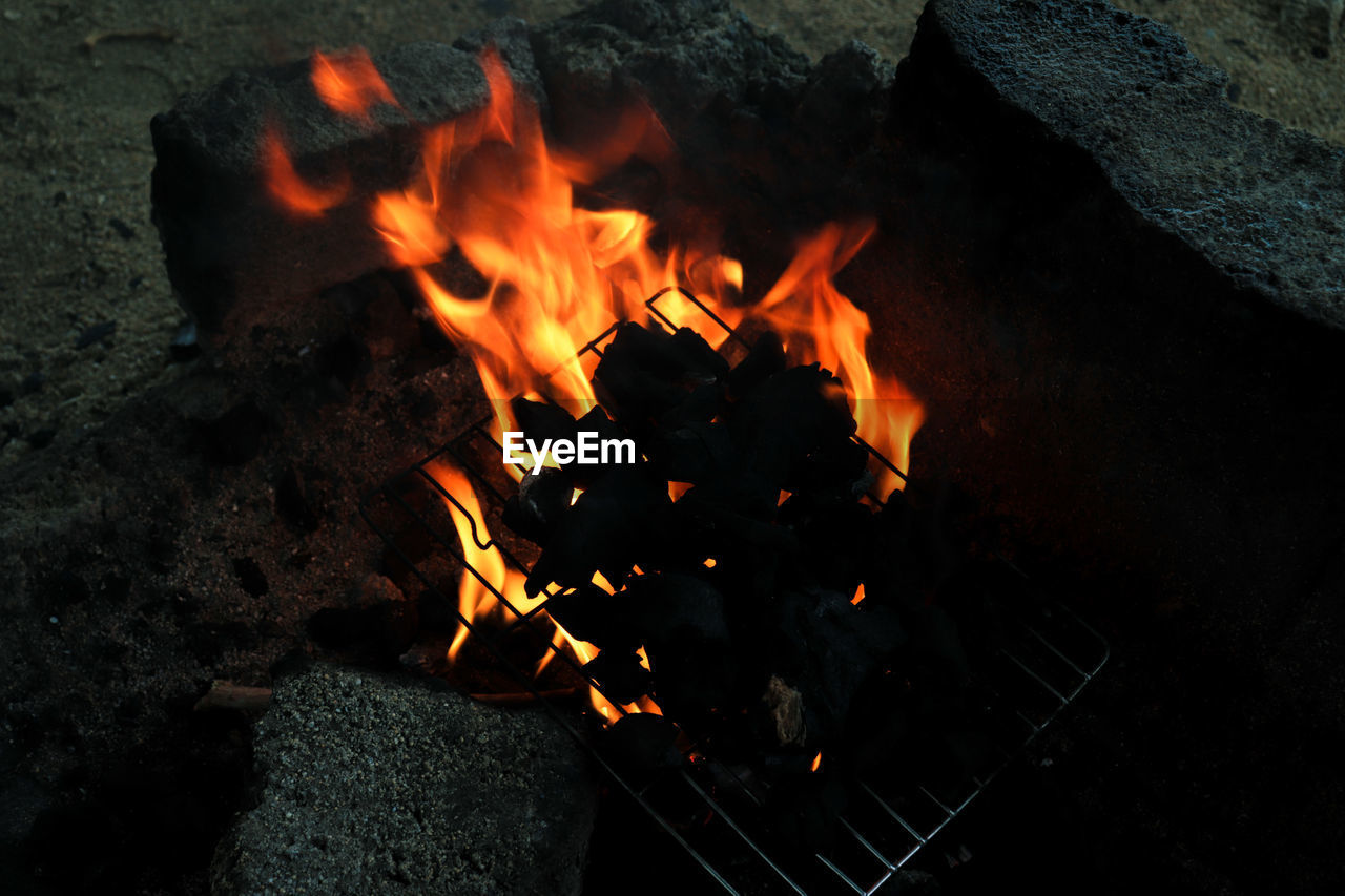 HIGH ANGLE VIEW OF FIRE BURNING IN CAMPFIRE