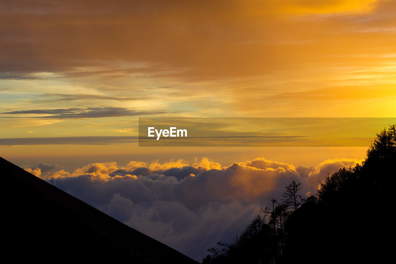 sky, cloud - sky, sunset, beauty in nature, scenics - nature, orange color, silhouette, tranquility, tranquil scene, no people, nature, tree, idyllic, plant, outdoors, low angle view, non-urban scene, dramatic sky, cloudscape