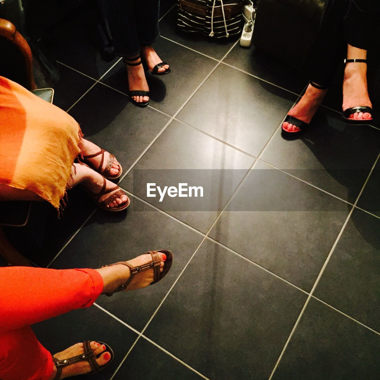 Low Section Of Women Sitting On Black Tiled Floor
