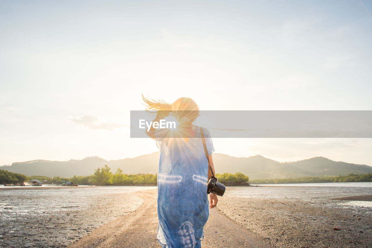 Woman Standing At Lakeshore Against Sky