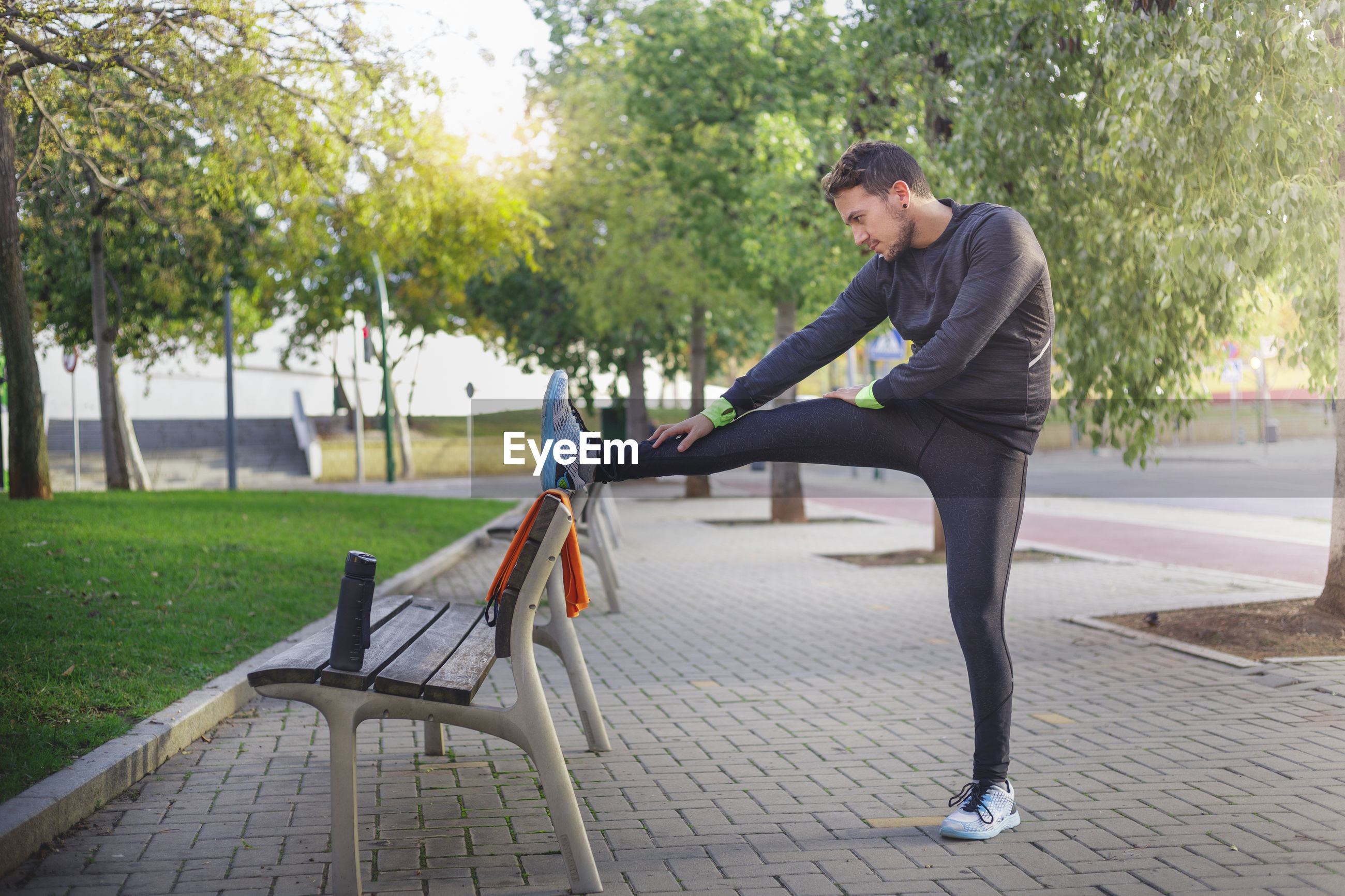 Side view of young man doing exercising for streching in a park
