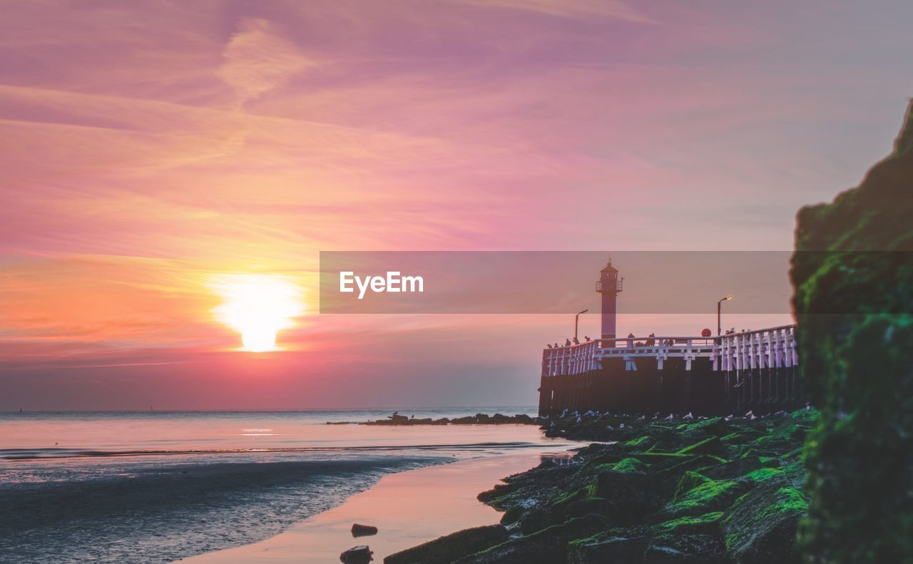 sky, sunset, water, sea, scenics - nature, orange color, sun, cloud - sky, beauty in nature, nature, land, beach, architecture, tranquil scene, no people, horizon over water, tranquility, outdoors, industry
