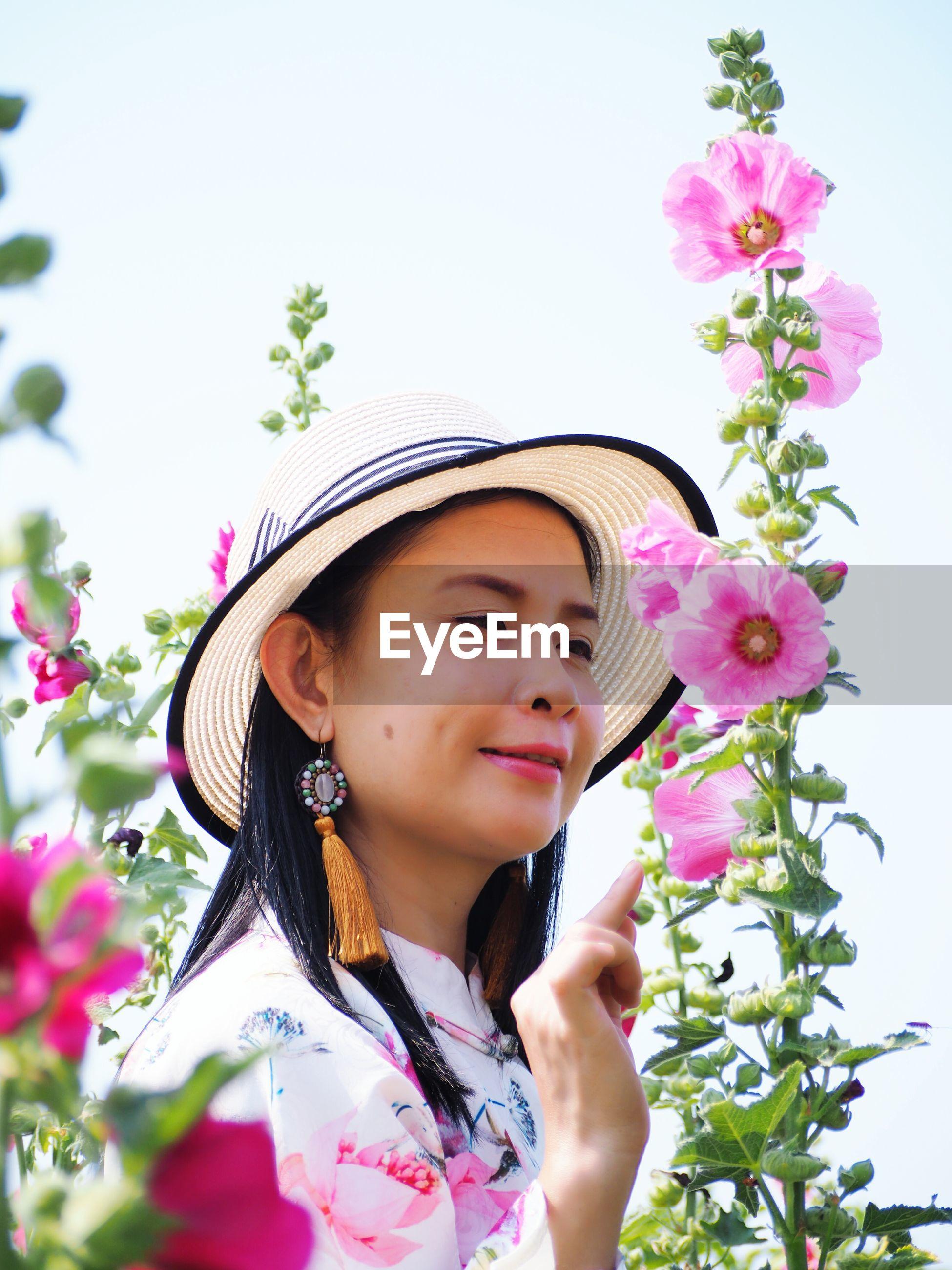 Smiling woman touching pink flowering plants
