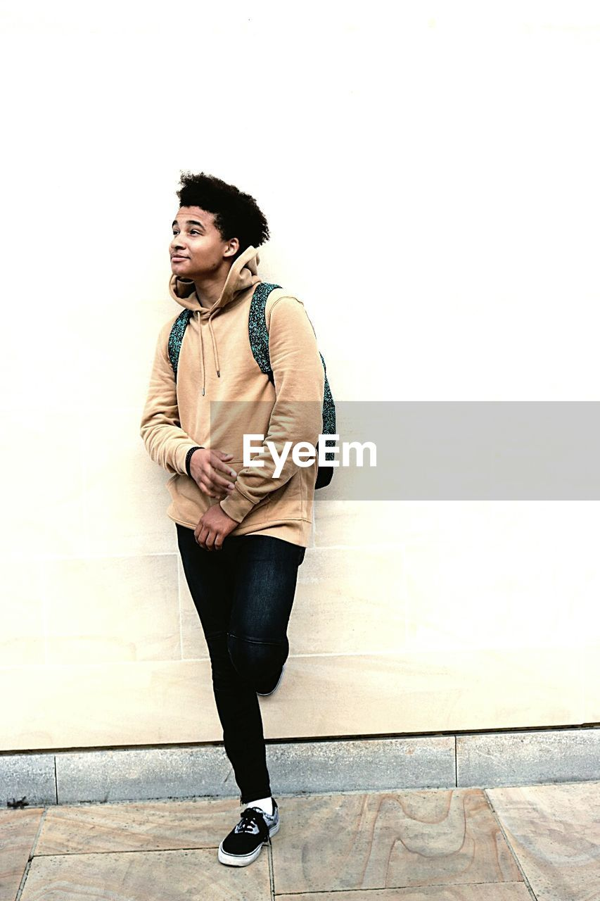 Full length of young man looking away while leaning on wall