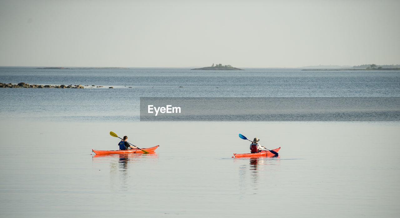 Men Kayaking In Sea Against Clear Sky