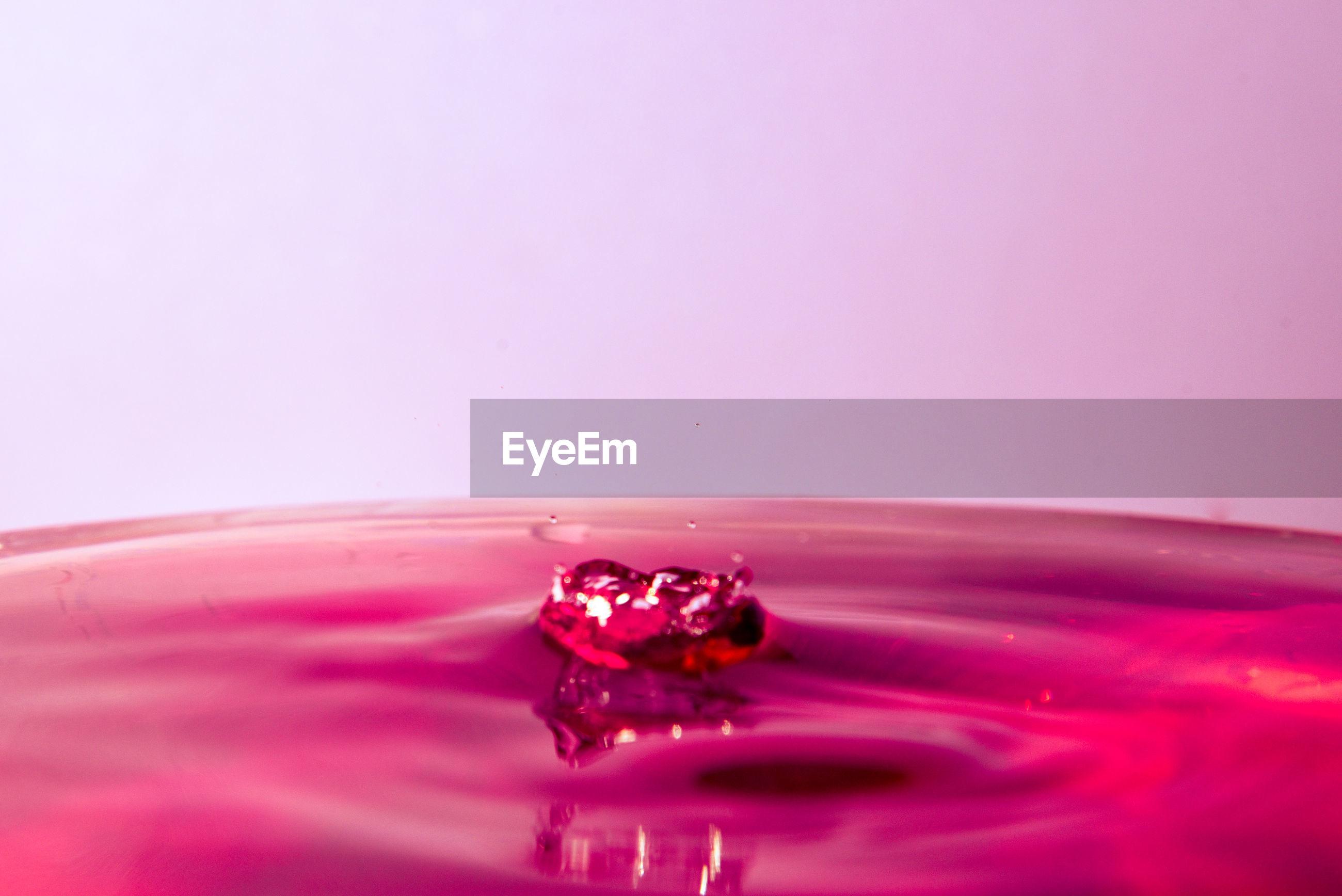 CLOSE-UP OF WATER SPLASHING ON PINK BACKGROUND
