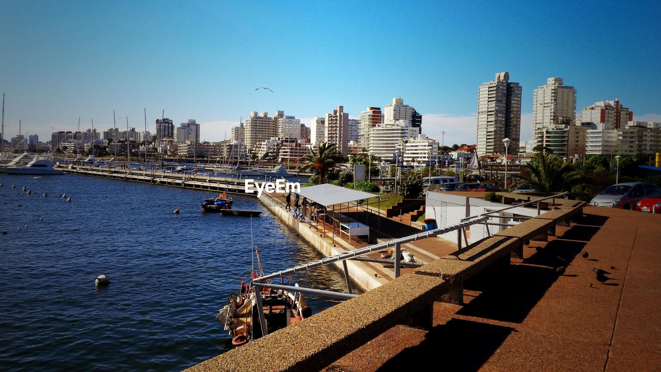 architecture, built structure, building exterior, city, skyscraper, day, clear sky, outdoors, cityscape, water, transportation, blue, travel destinations, nautical vessel, sunlight, sky, no people, sea, urban skyline, nature