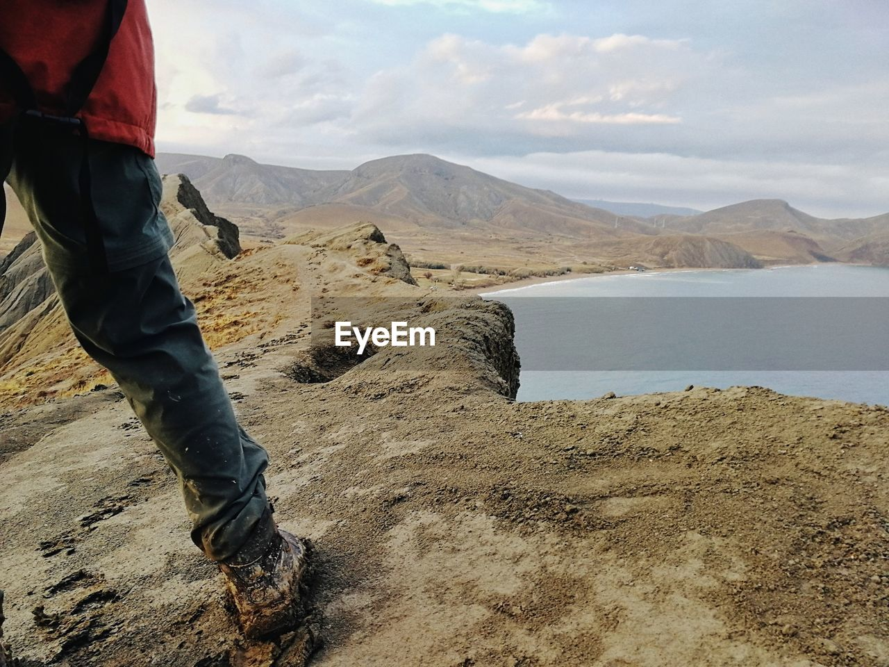 MIDSECTION OF MAN IN MOUNTAINS AGAINST SKY