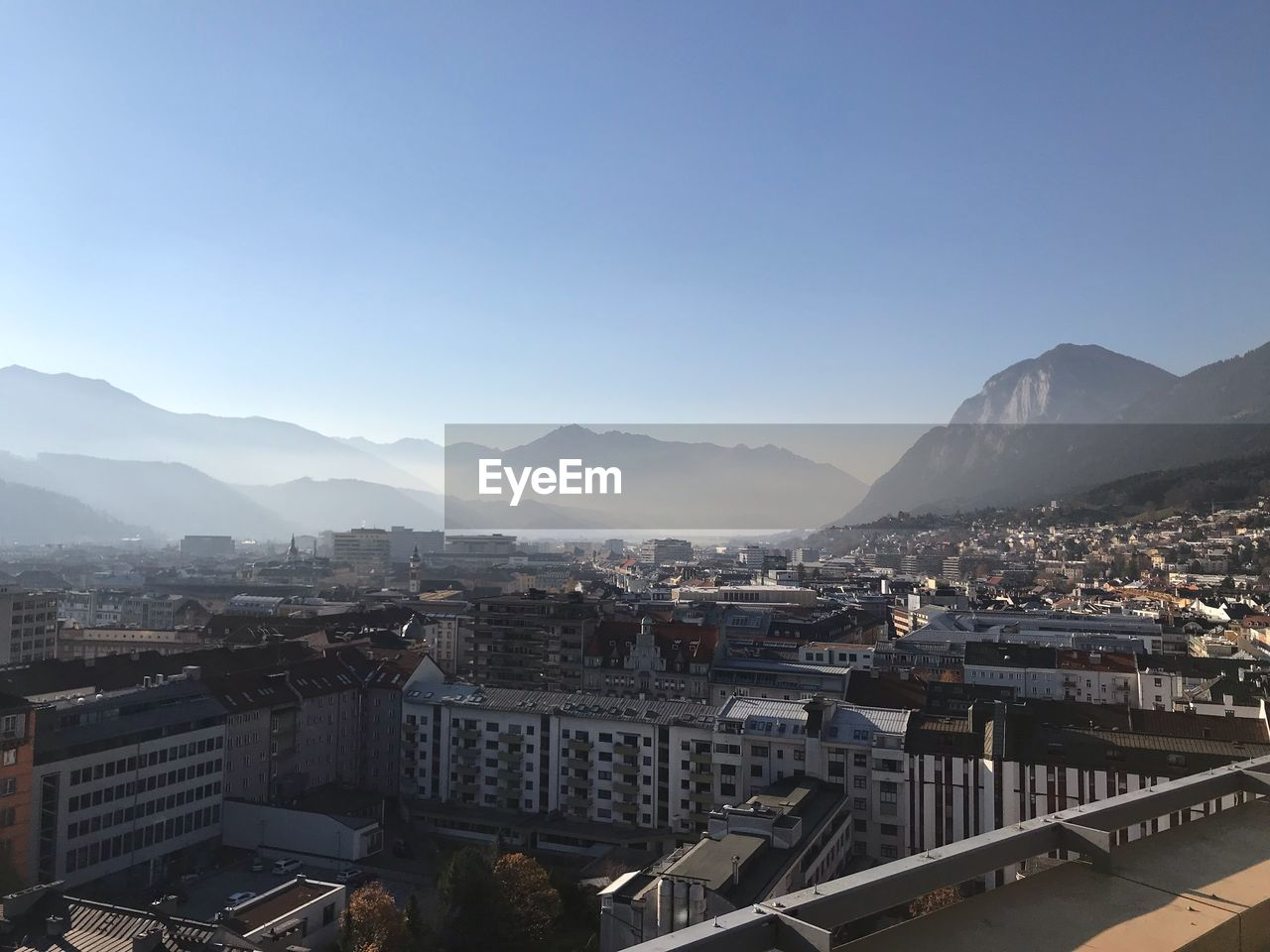 building exterior, built structure, architecture, mountain, sky, city, residential district, building, clear sky, copy space, mountain range, nature, cityscape, no people, day, sunlight, town, high angle view, outdoors, townscape, settlement