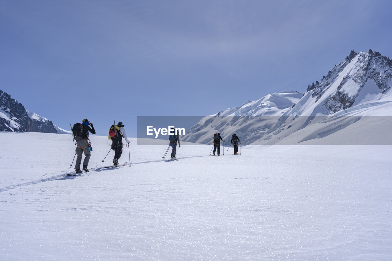 Full length of ski mountaineers walking on snowcapped mountain against sky