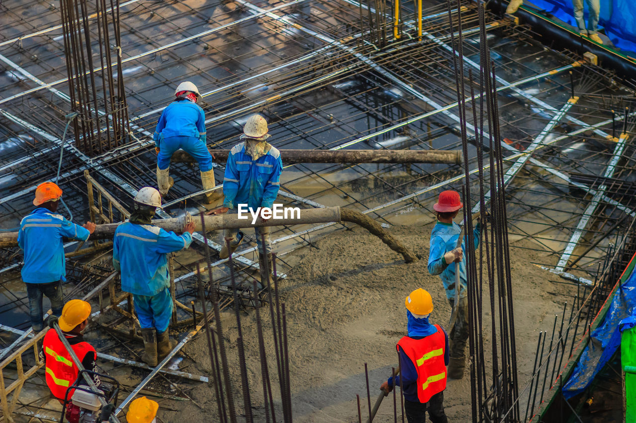 group of people, working, occupation, headwear, protective workwear, cooperation, teamwork, coworker, hardhat, industry, helmet, men, protection, hat, people, full length, high angle view, standing, adult, mature men