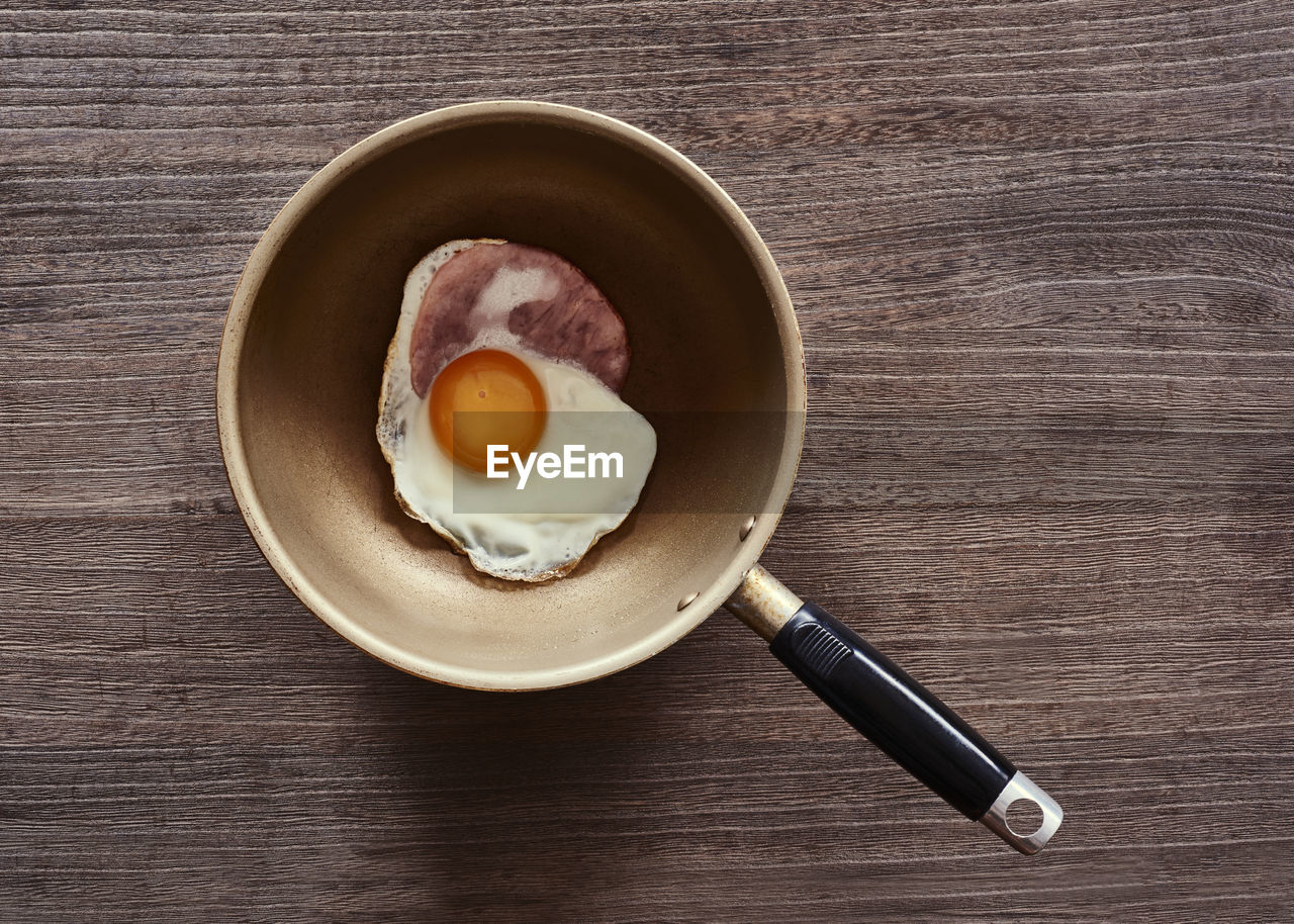High Angle View Of Fried Egg In Frying Pan On Table
