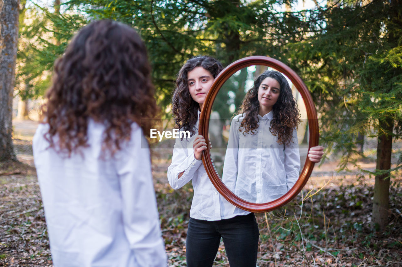 Woman reflecting in mirror held by friend while standing on field