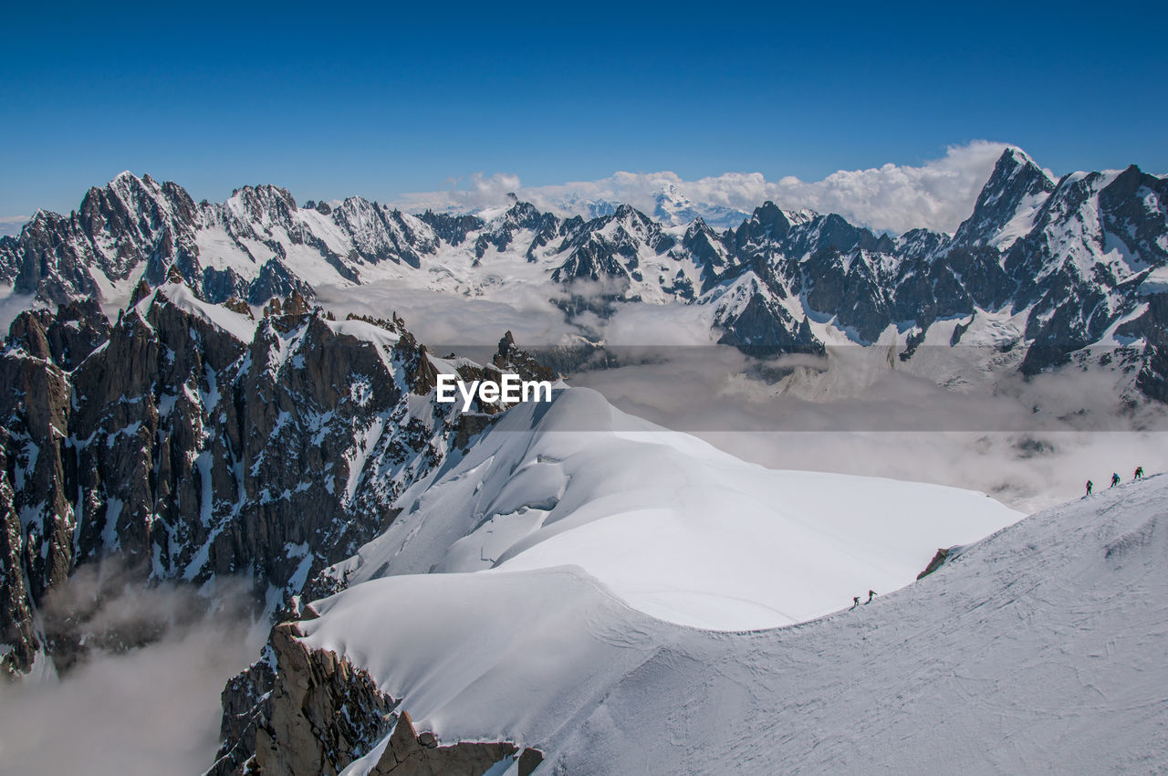 Snowy peaks and mountaineers in a sunny day at the aiguille du midi, near chamonix, france.