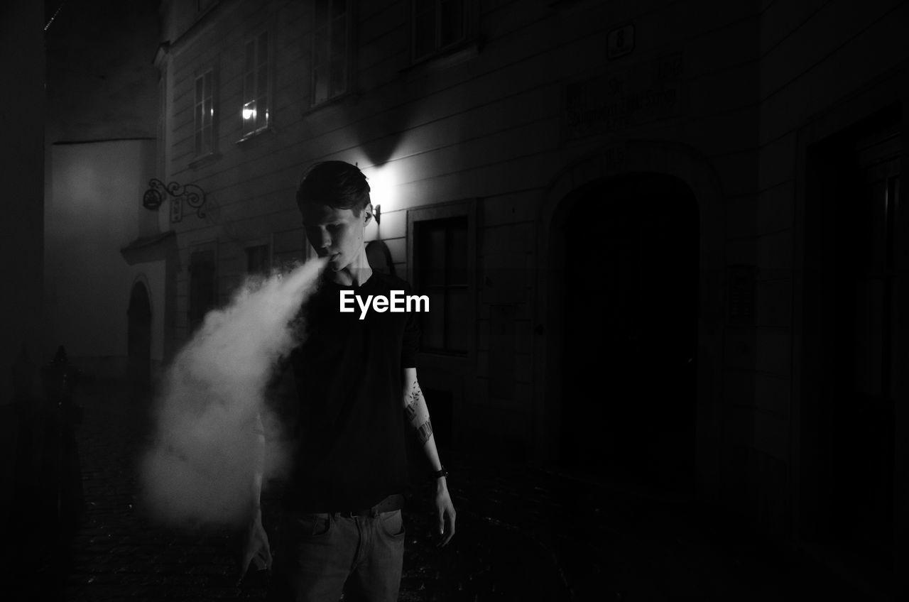 Man exhaling smoke at night