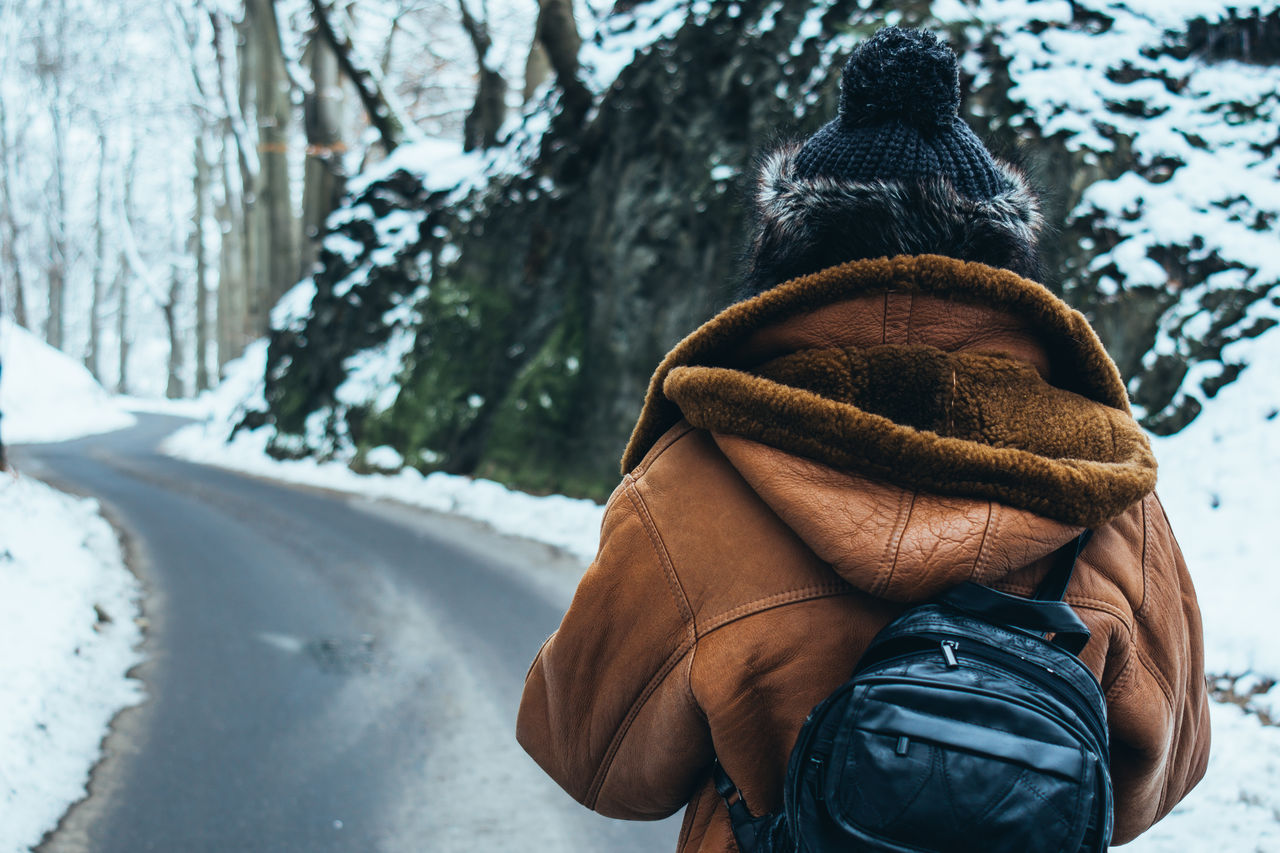 Rear view of person with backpack standing on empty road in snow covered forest