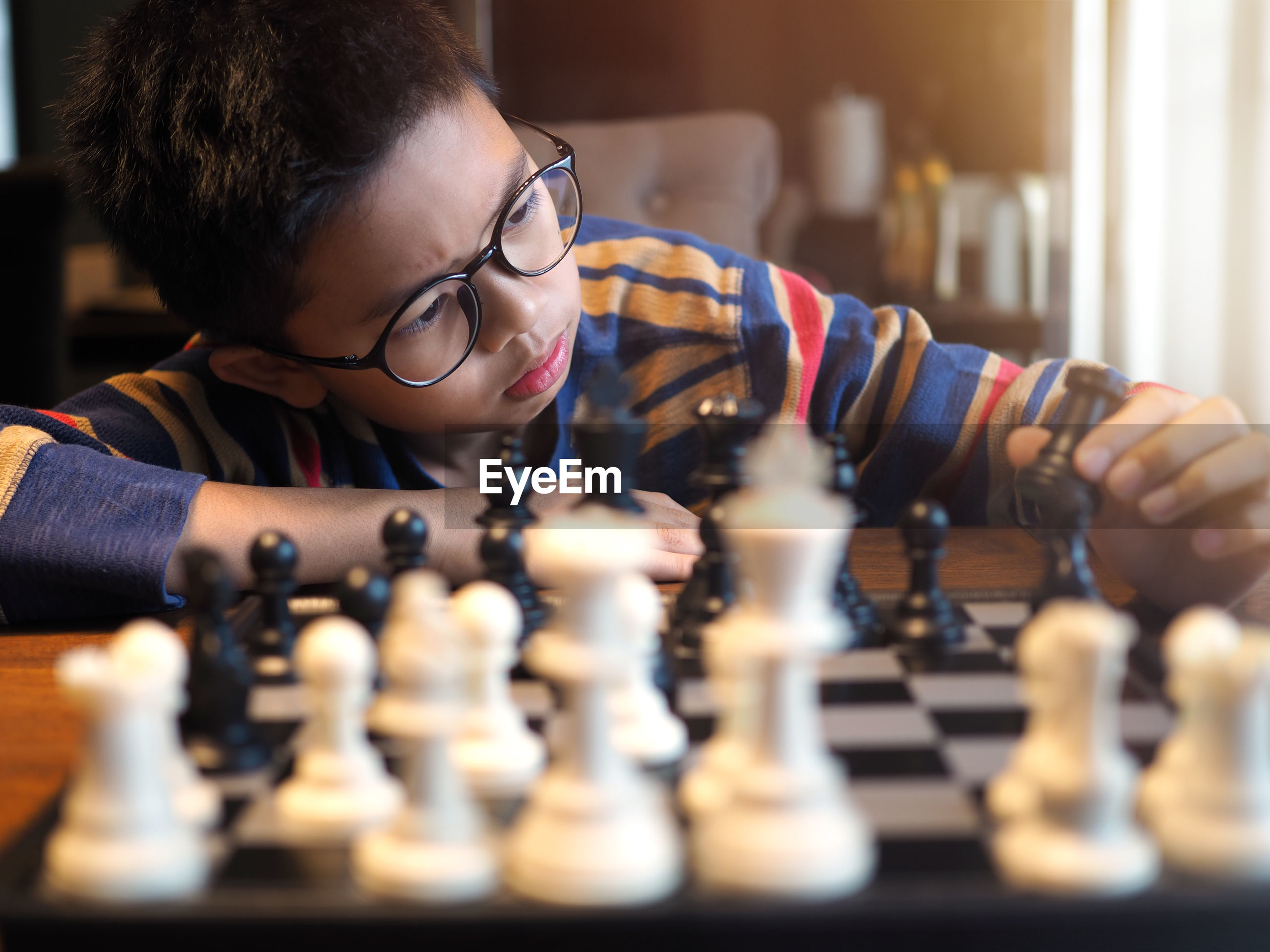 Serious boy wearing eyeglasses while playing chess at home