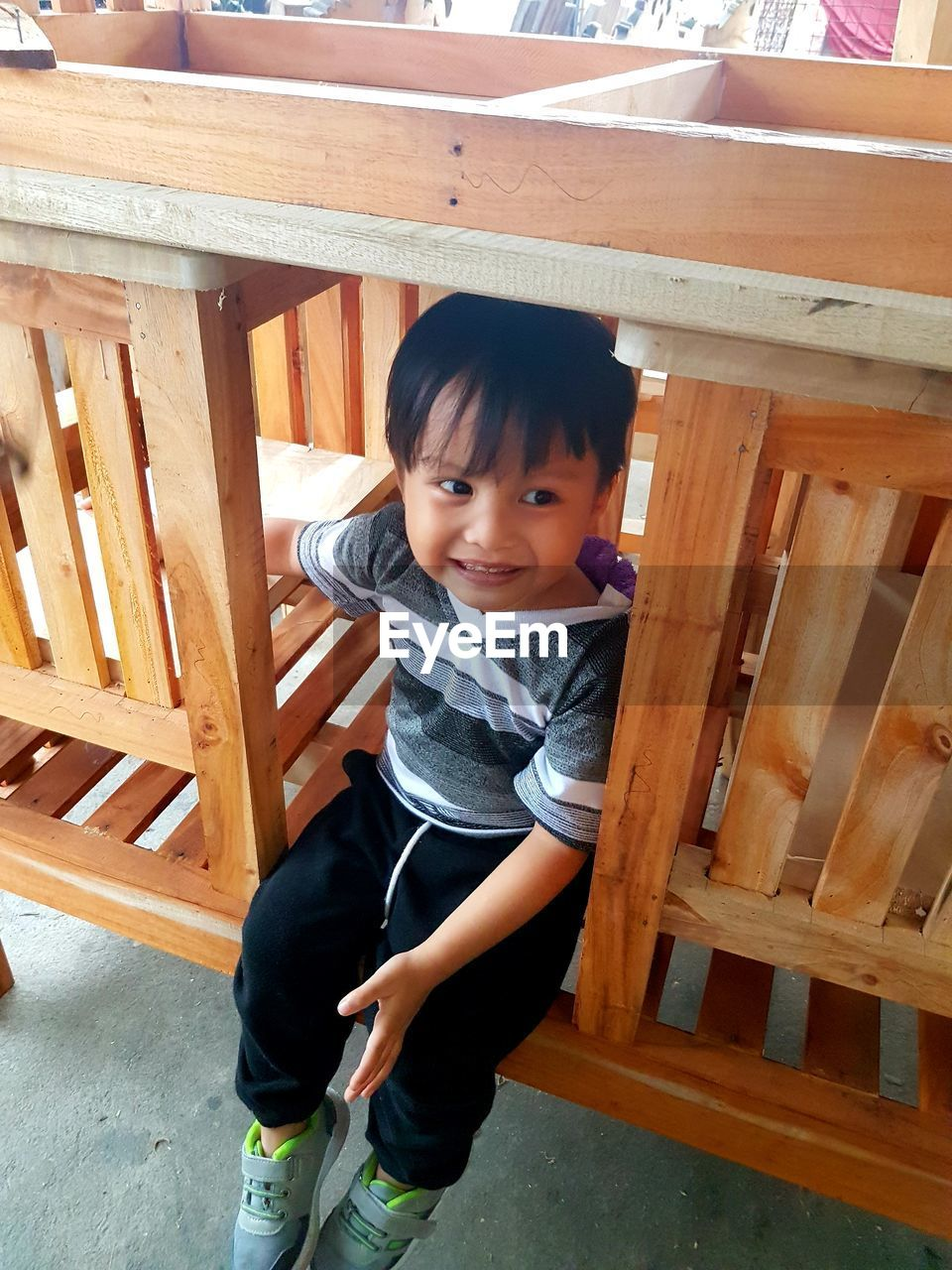 High angle view of cute boy sitting on wood
