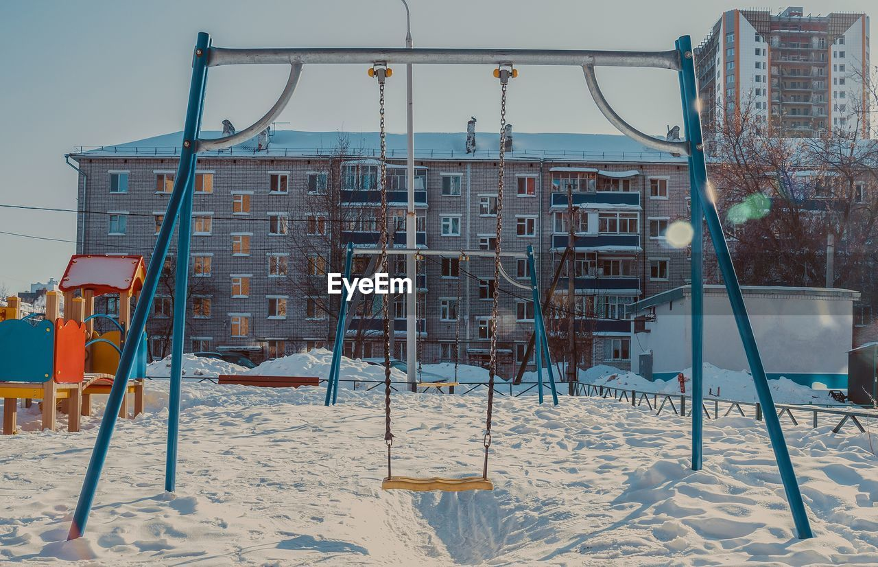 winter, cold temperature, land, snow, nature, sand, playground, day, architecture, built structure, swing, childhood, outdoor play equipment, outdoors, sky, absence, jungle gym, slide