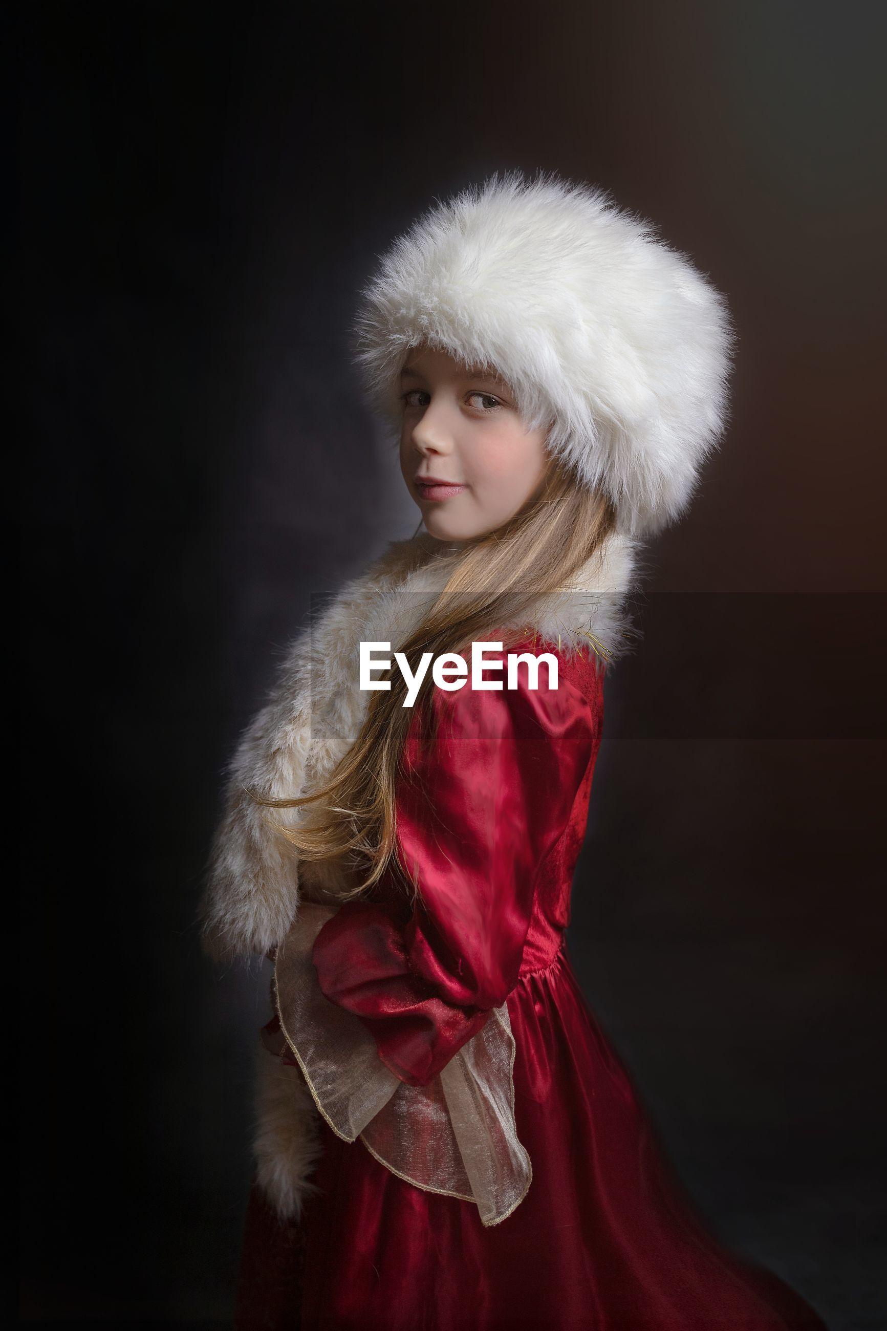 Side view portrait of girl wearing fur hat against black background