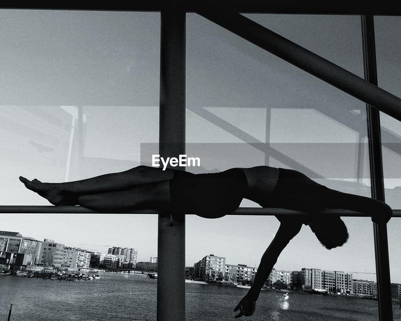 Woman lying on window sill against sky