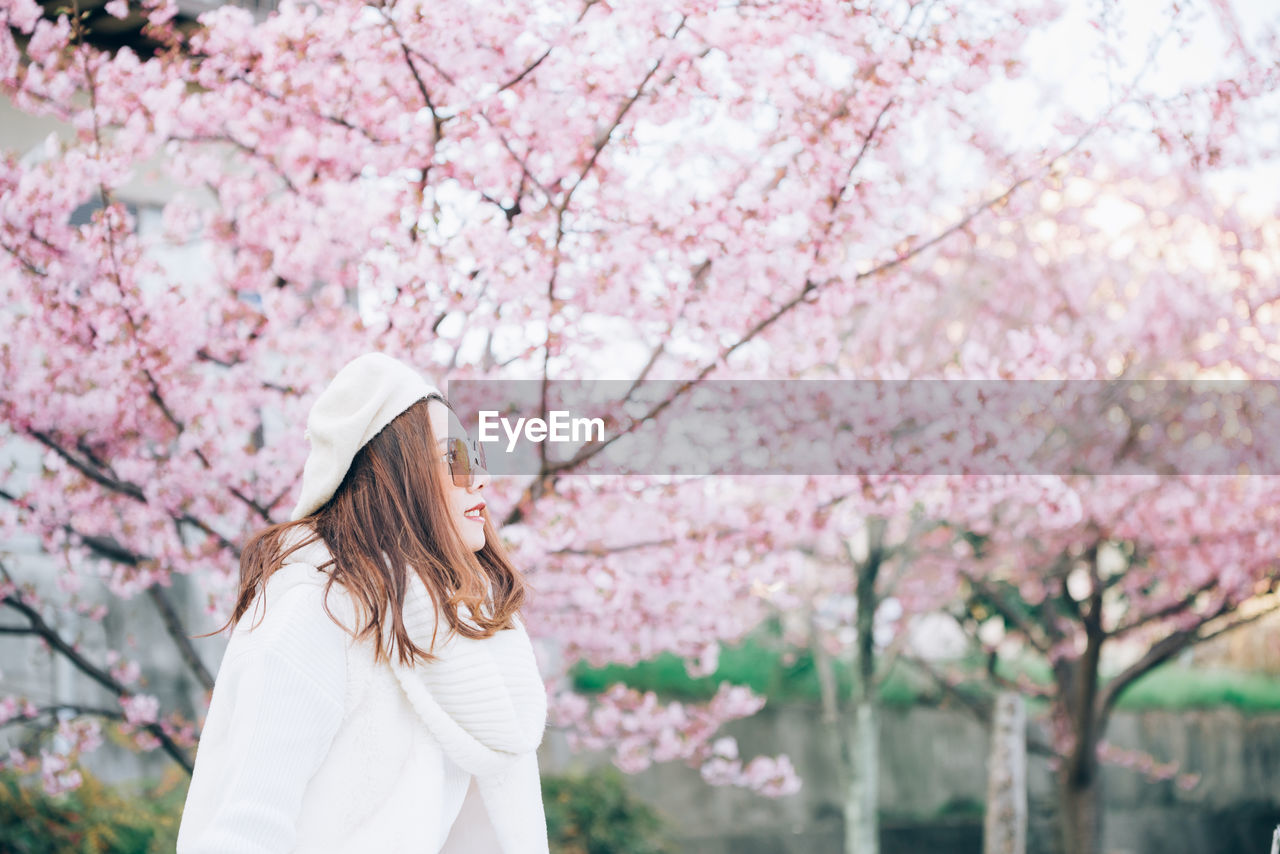 Woman in sunglasses standing against pink cherry blossom tree
