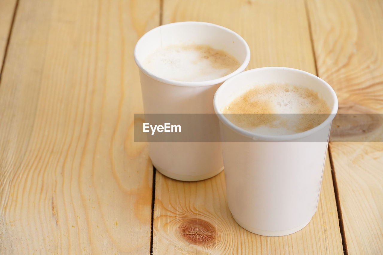 refreshment, coffee, drink, coffee - drink, cup, food and drink, mug, coffee cup, table, still life, wood - material, freshness, indoors, high angle view, no people, close-up, frothy drink, cappuccino, white color, hot drink, latte, non-alcoholic beverage, crockery, temptation, froth