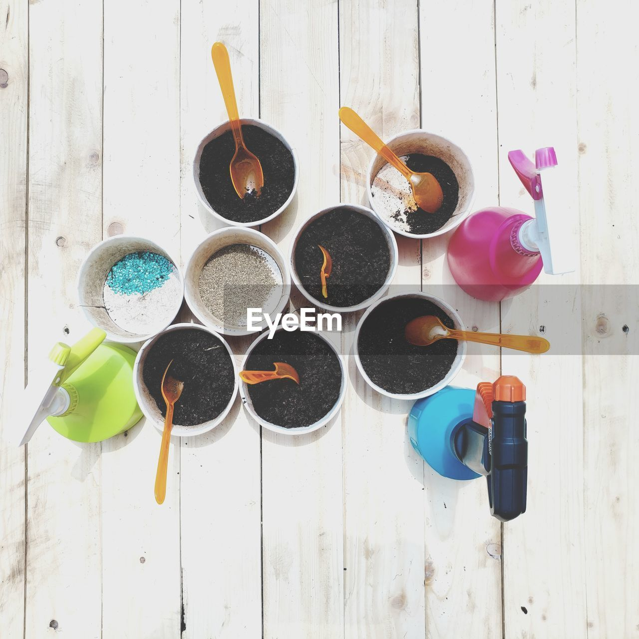 no people, table, high angle view, indoors, still life, directly above, variation, multi colored, choice, wood - material, kitchen utensil, group of objects, cup, food and drink, circle, mug, day, spoon, container, eating utensil