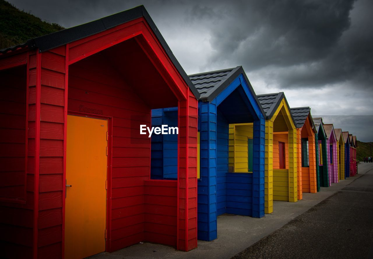 multi colored, architecture, built structure, sky, cloud - sky, in a row, red, beach hut, building exterior, no people, side by side, nature, outdoors, hut, building, overcast, beach, land, day