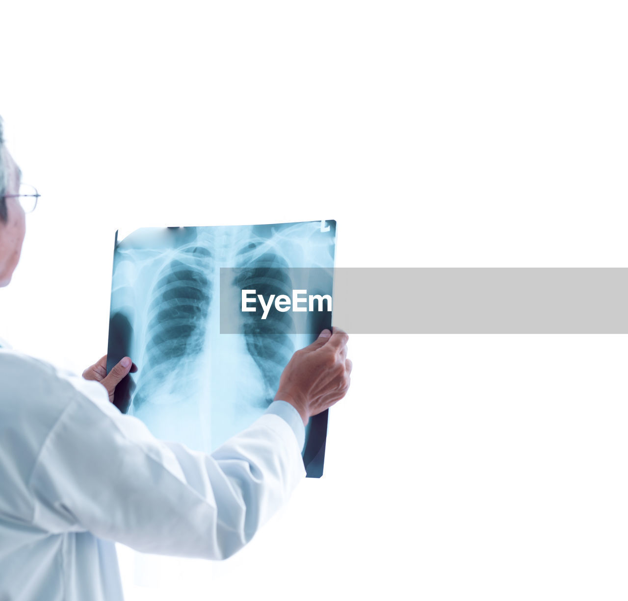 Midsection of male doctor analyzing x-ray against white background
