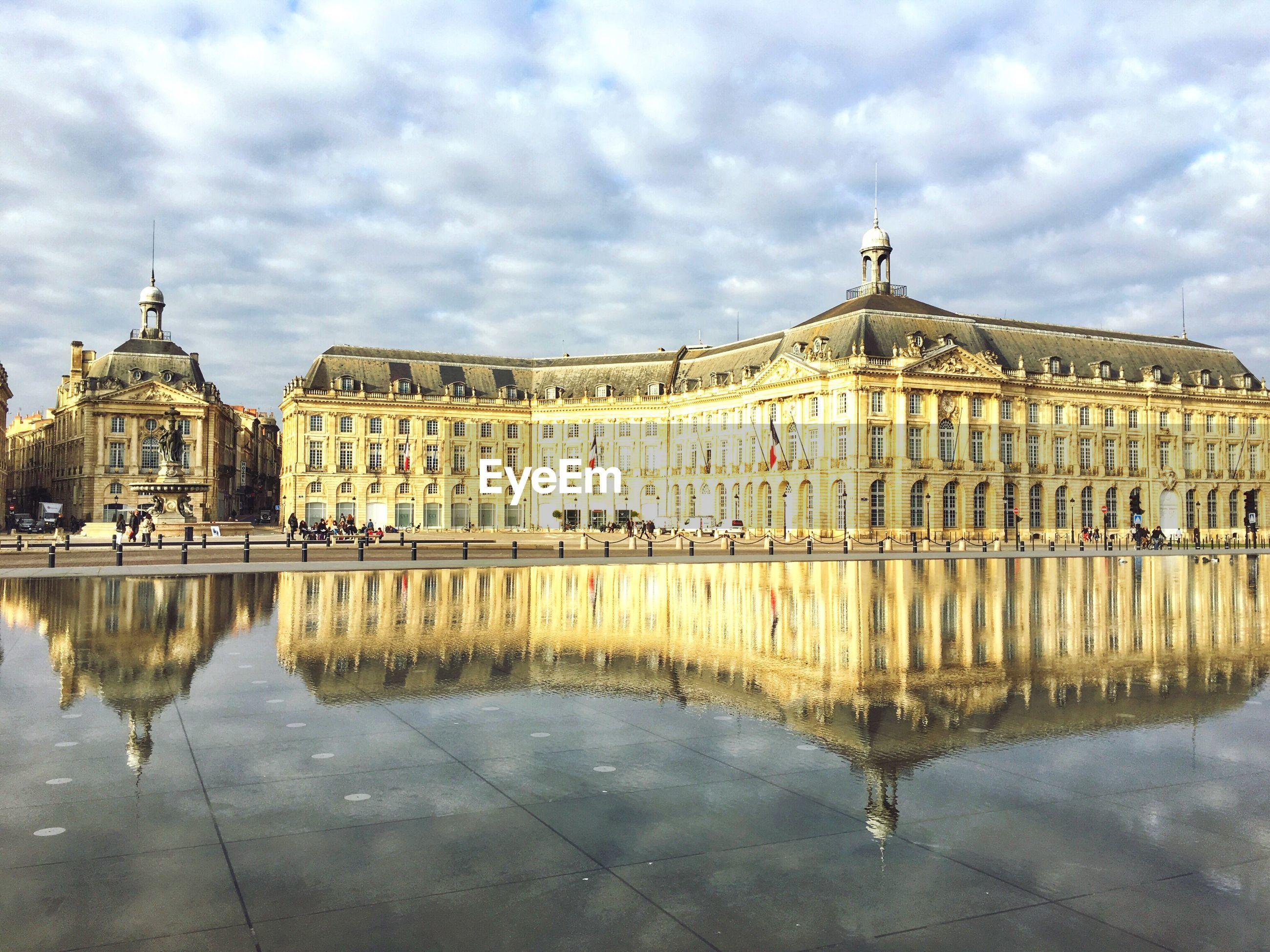 Place de la bourse by miroir d eau against cloudy sky