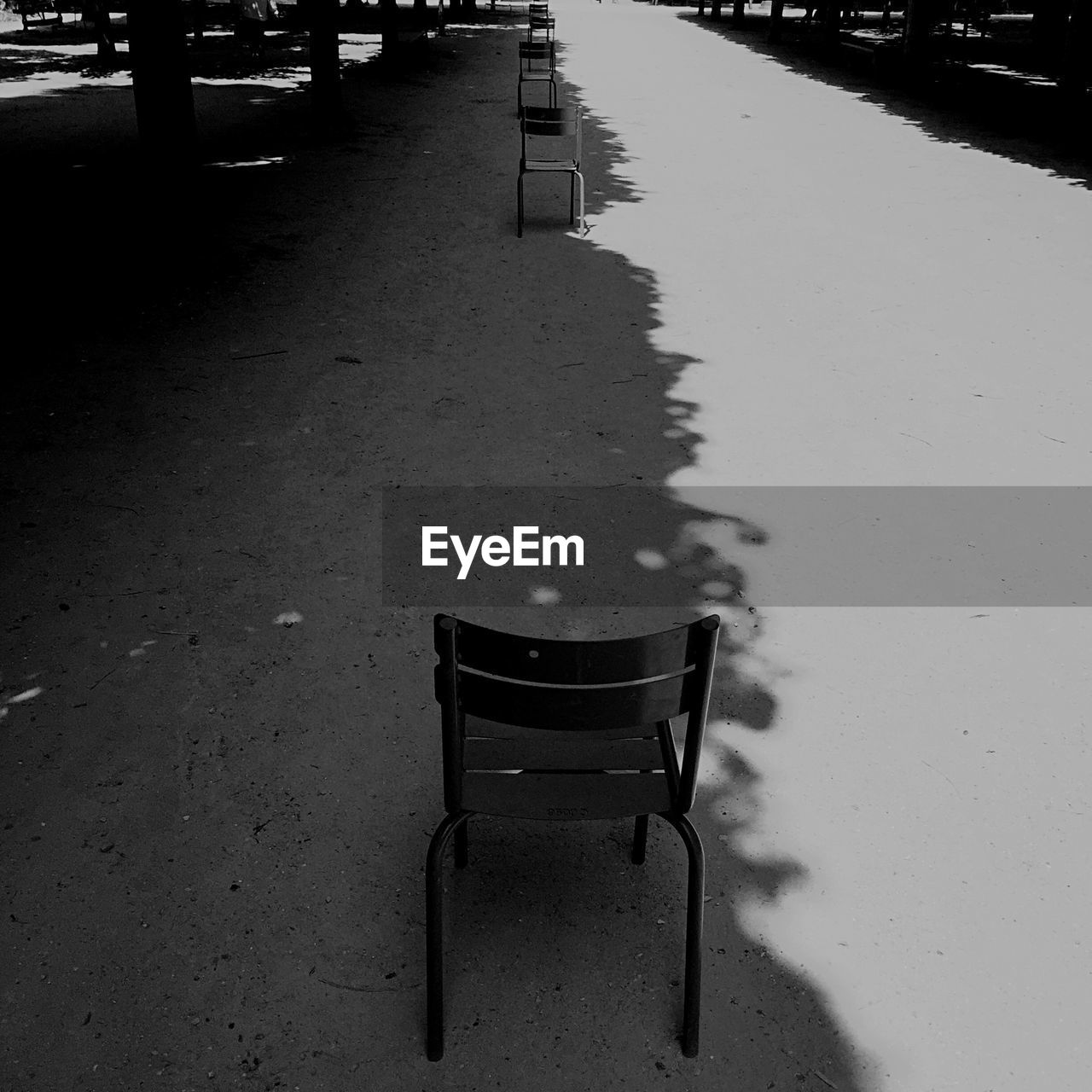 Row Of Empty Chairs On Footpath