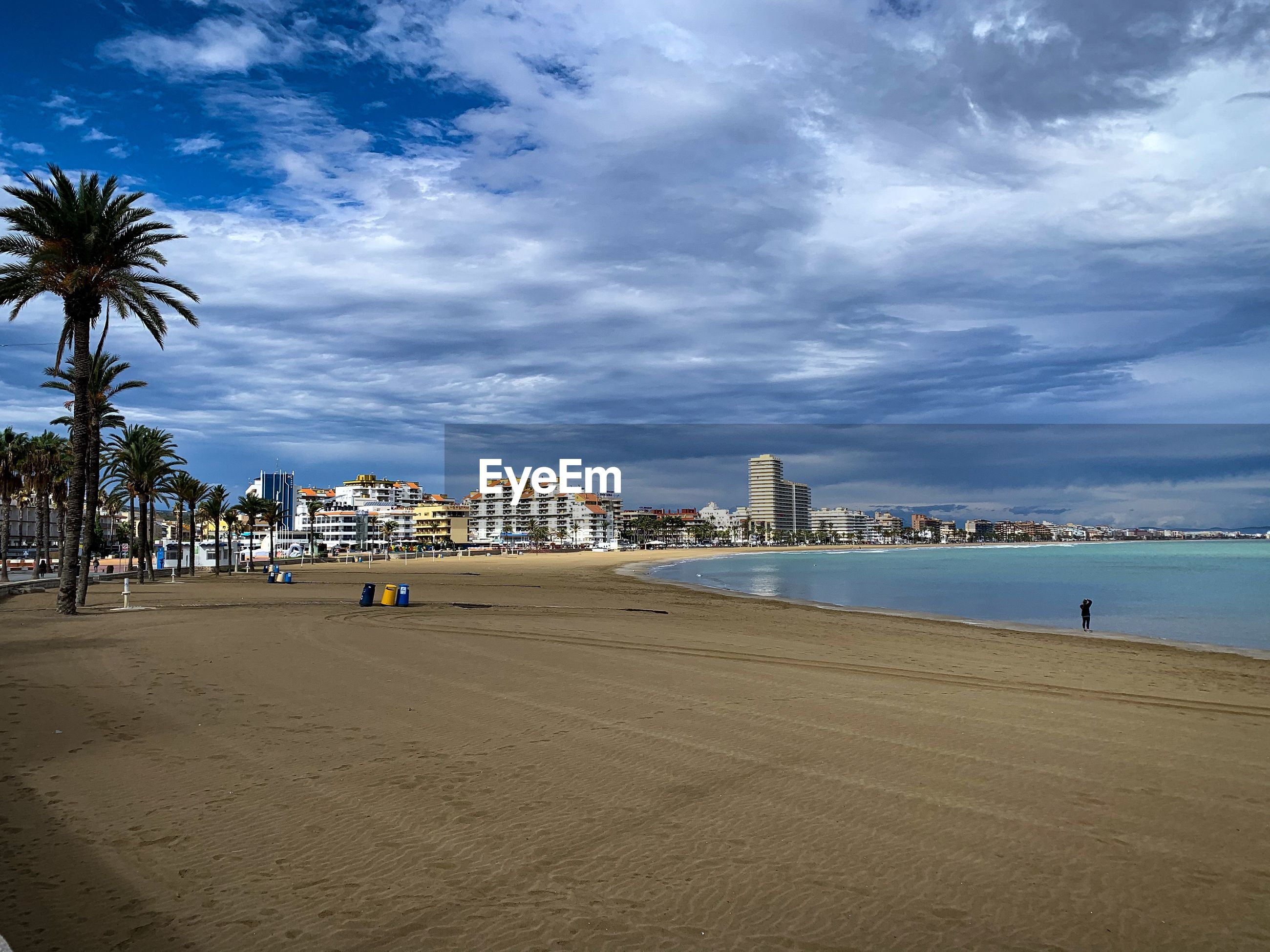 SCENIC VIEW OF BEACH BY CITY AGAINST SKY