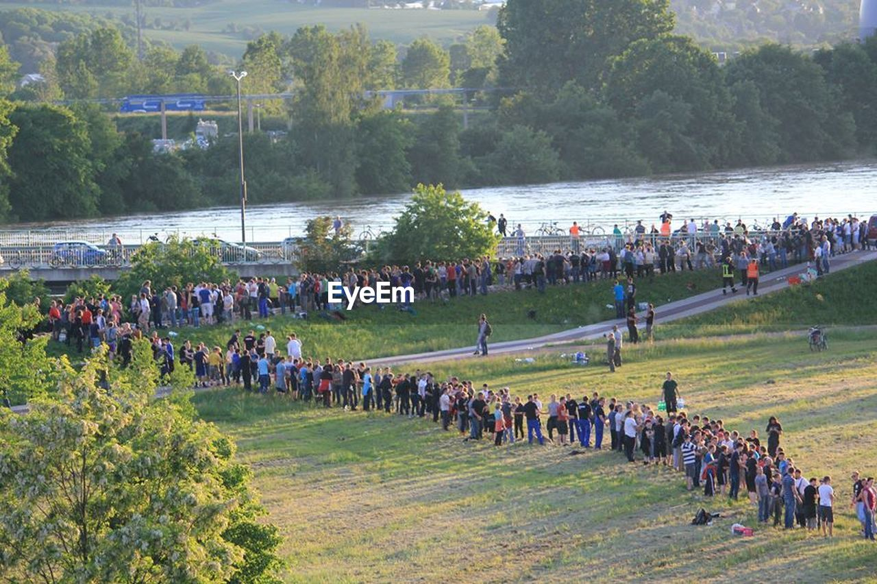 large group of people, real people, men, nature, day, leisure activity, mixed age range, outdoors, tree, crowd, women, water, lifestyles, grass, togetherness, beauty in nature, people, adult