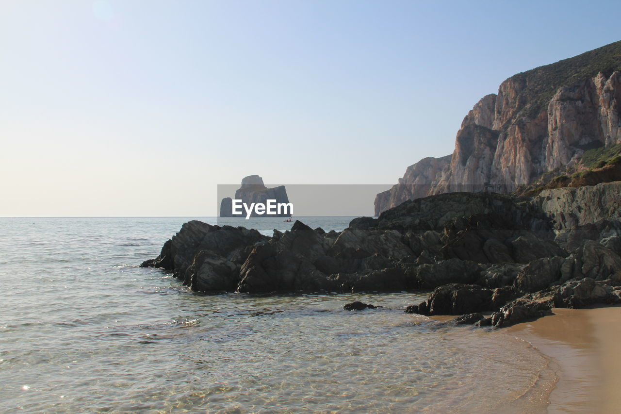 sea, rock - object, rock formation, nature, clear sky, tranquility, water, scenics, no people, beauty in nature, outdoors, sky, day, horizon over water