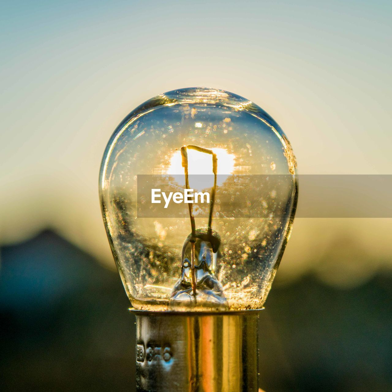 Close-Up Of Light Bulb Against Sky During Sunset