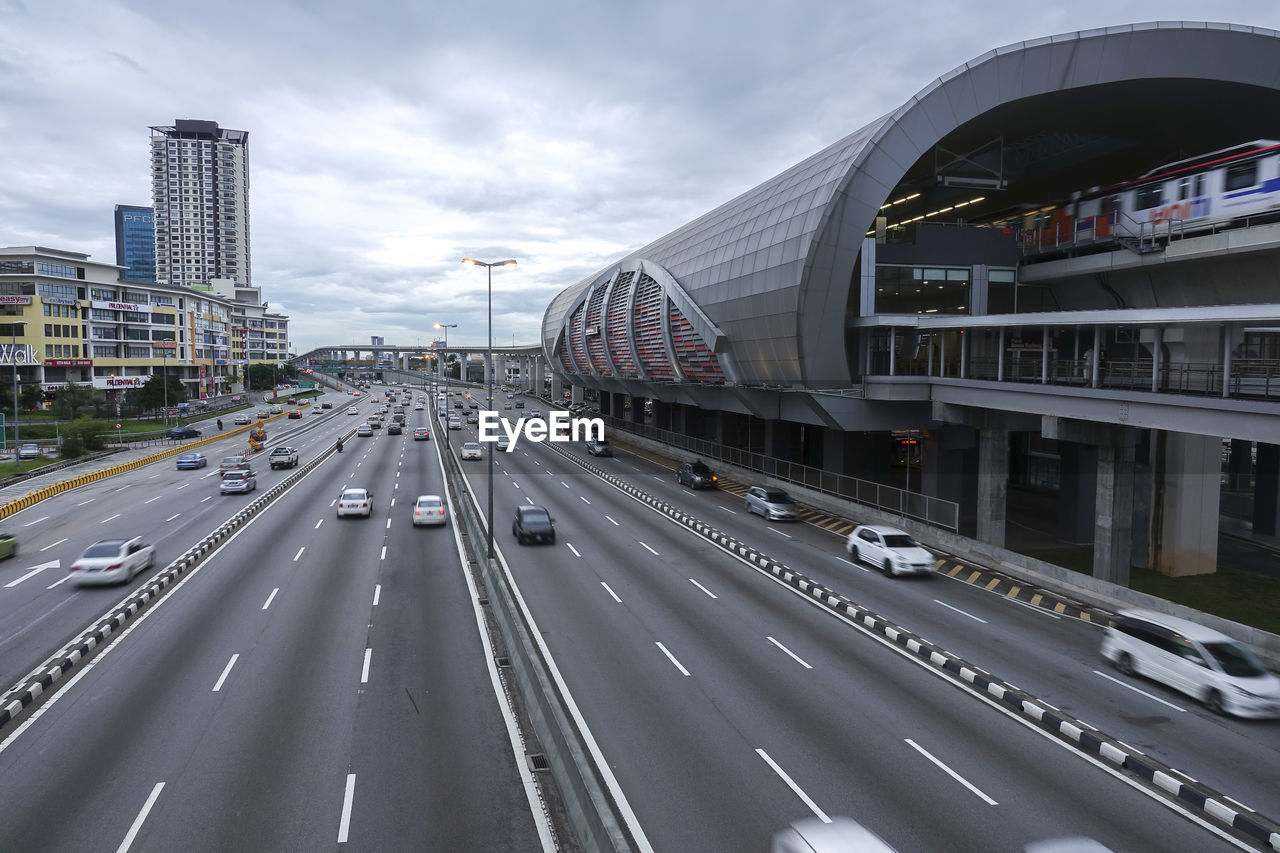 road, transportation, architecture, built structure, city, building exterior, land vehicle, symbol, sky, marking, mode of transportation, road marking, sign, cloud - sky, highway, motor vehicle, car, direction, the way forward, connection, bridge - man made structure, no people, office building exterior, modern, multiple lane highway, outdoors, diminishing perspective, skyscraper, cityscape